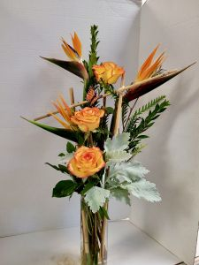 Bamboo frame, bright colored roses, birds of paradise and tropical greens.   colors and greens may vary.